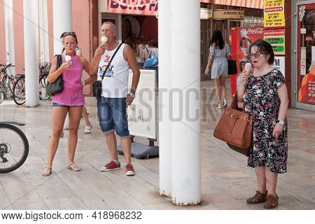 Szeged, Hungary - July 21, 2018: Three People, A Couple Of Lovers And A Senior Old Woman Eating Ice
