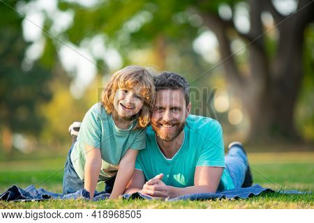 Father And Son Smiling Against Summer Blurred Background At The Park.