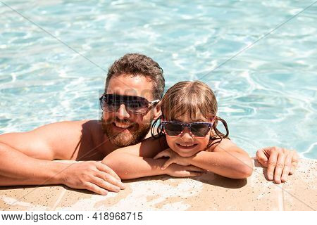 Father And Son In Pool. Summer Vacation Concept. Happy Family In Swimming Pool. Pool Party. Child Wi