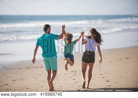 Happy Family Holidays. Joyful Father, Mother, Baby Son Walk Of Sea Sand Beach. Active Parents And Pe