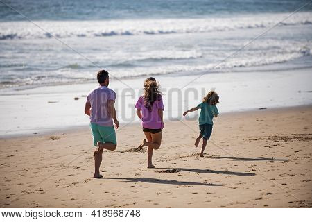 Back View Of Cheerful Family Running On The Beach. Happy Mother Father With Child Son, Jogging Durin