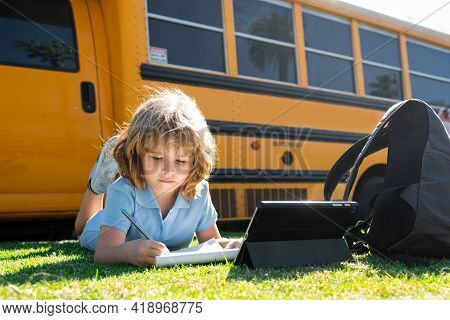 Smart Schoolboy On Laying On Grass With Digital Tablet At School Park. Child Using Gadgets To Study