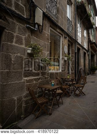 Charming Old Vintage Historic Rock Brick Stone House Facade Wall With Wooden Chair And Table Decorat