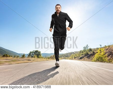 Full length portrait of a man in black tracksuits running outdoors on an asphalt road