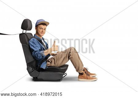 Male teenager in a car seat with a seatbelt showing thumbs up isolated on white background