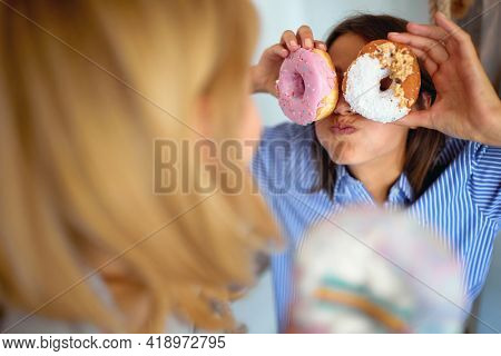 A girl making funny grimaces using delicious donuts while spending time with her friend in a cheerful atmosphere in a pastry shop. Pastry shop, dessert, sweet