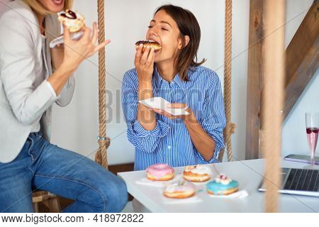 Two female friends enjoy eating delicious donuts in a pleasant atmosphere in a pastry shop. Pastry shop, dessert, sweet