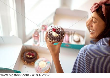 A beautiful girl in a pleasant atmosphere in a pastry shop is passionately looking at a delicious donut she hardly waits try. Pastry shop, dessert, sweet