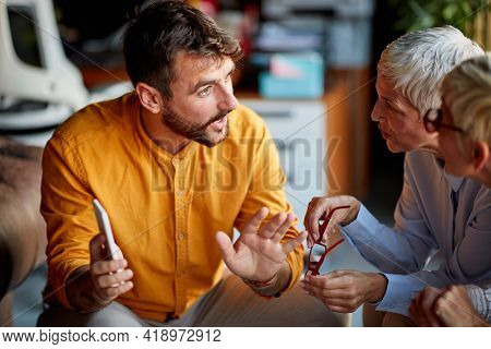 Two older business women of similar appearance and young male colleague have an interesting talk during a break in a friendly atmosphere at workplace. Business, office, job