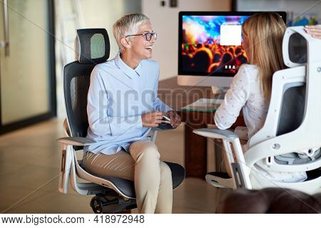 An elderly business woman chatting with her young female colleague while they are sitting in a pleasant atmosphere at the office. Business, office, job