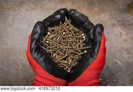 Carpenter wearing protective gloves holding a handful of tapered shank screws in cupped hands against rusty metal background