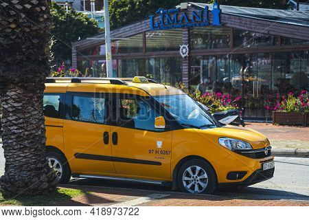 Alanya, Turkey  - April 13  2021: Yellow Taxi Fiat Doblo    Is Parked  On The Street On A Warm Summe
