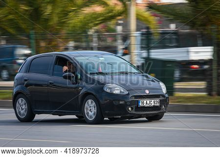 Alanya, Turkey - April 16 2021:   White Fiat Punto   Is Driving Fast On The Street On A Warm Summer