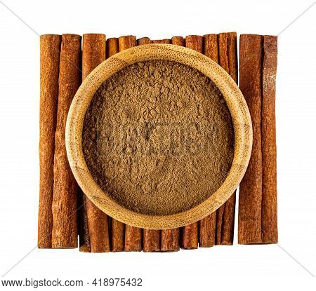 Bamboo Bowl With Ground Cinnamon On Few Cinnamon Sticks Isolated On White Background. Top View