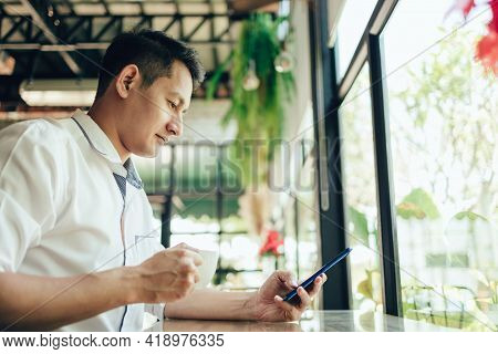 Young Businessman Working And Using Smart Phone And Notebook Computer In Workplace. Young Freelance