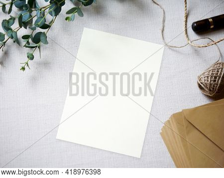 Top View Mockup Blank Card, For Greeting, Wedding Invitation Template With Eucalyptus Leaves On Clot