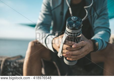 Sport Man Sitting After Running And Holding Water Bottle Drink. Sport Thirsty And Resting After Exer