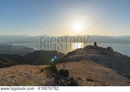 A Man Sits On A High Mountain Cliff And Overlooks The Sunrise And The Horizon. A Concept For Hope, P