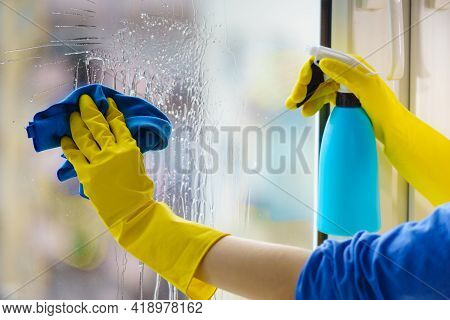 Female Hand In Yellow Gloves Cleaning Window Pane With Rag And Spray Detergent. Cleaning Concept