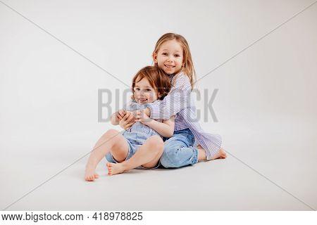 Older Sister Hugs Younger Sister, And She Runs Away. Restless Children.
