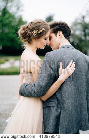 Groom Hugs And Almost Kisses Bride In The Park. Lake Como, Italy