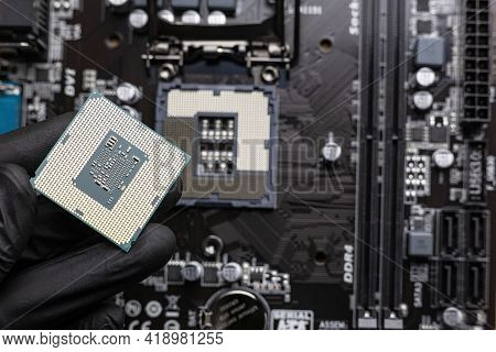 Central Processing Unit (central Processing Unit) In A Man's Hand In A Black Glove - Close-up, With