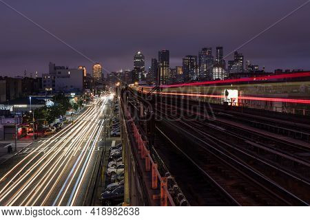 New York, New York / Usa - October 11 2018: A Subway Passing An Elevated Bridge With The Skyline Of