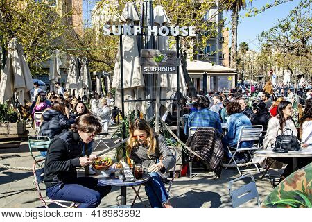 Spain, Barcelona, March, 2021: People Dine On The Open Verandas Of Cafes And Restaurants On The Barc