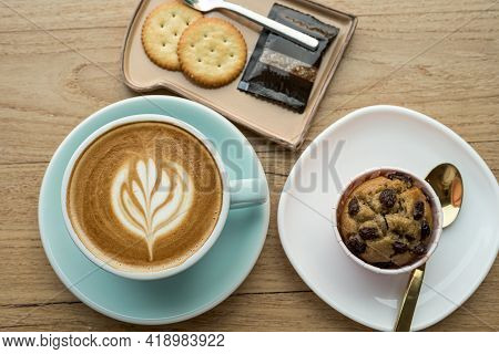 Close-up Of Hot Coffee Latte With Latte Art Milk Foam In Cup Mug And Homemade Banana Cup Cake,biscui
