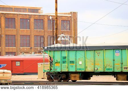 April 26, 2021 In Cheyenne, Wy:  Union Pacific Rail Cars On The Railroad Yard With The Warehouse And