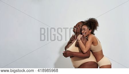 Happy Slim And Overweight African American Women In Underwear Hugging And Laughing While Posing Toge