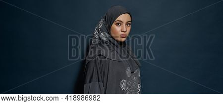 Young Arabian Girl In Hijab Looking At Camera While Posing Sideways On Dark Blue Background With Cop