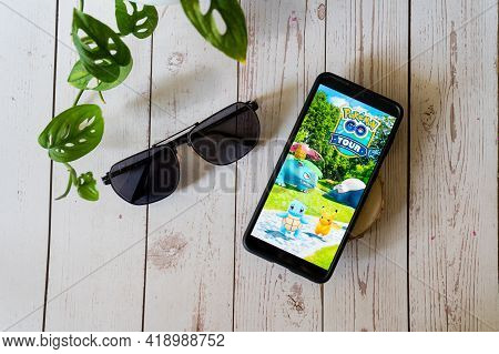 Famous Augmented Reality Virtual Game Pokemon Go Tour Playing On A Mobile Phone On A Wooden Table Ou
