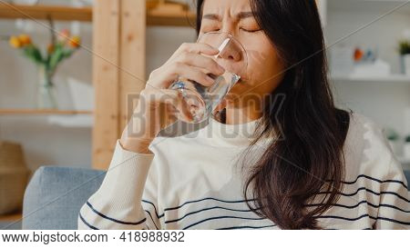 Sick Young Asia Woman Holding Pill Glass Of Water Take Medicine Sit On Couch At Home. Girl Taking Me