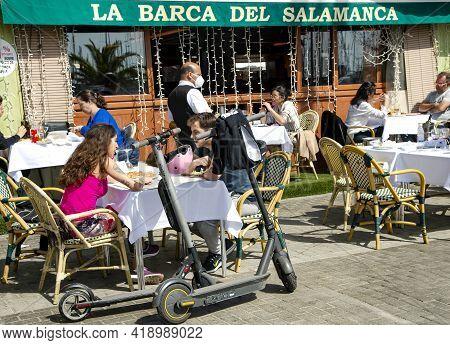 Spain, Barcelona, March, 2021: People Dine On The Open Veranda Of Restaurant La Barca Del Salamanca