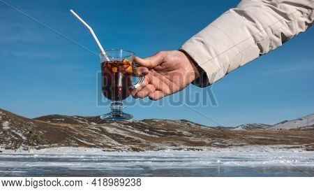A Glass With Hot Mulled Wine In A Man's Hand Against A Winter Landscape. Red Wine, Sliced Fruits, St