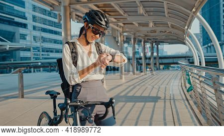 Asian Businesswoman With Backpack Bicycle Smiling Look Smartwatch In City Street Go To Work At Offic