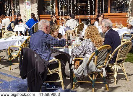 Spain, Barcelona, March, 2021: Family Dine On The Open Veranda Of Restaurant La Barca Del Salamanca
