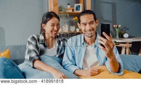 Happy Young Asian Couple Man And Woman Sit Couch Use Smartphone Facetime Video Call With Friends And