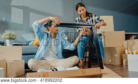 Happy Asian Young Attractive Couple Man And Woman Help Each Other Unpacking Box And Assemble Furnitu