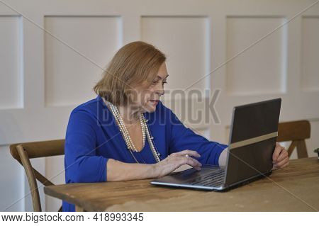 Old Person Using Computer In Home. . Mature Lady Sitting At Work Typing A Notebook Computer In An Ho