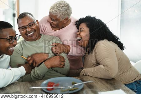 Happy African Family Having Fun After A Lunch Together At Home - Food And Parents Unity Concept