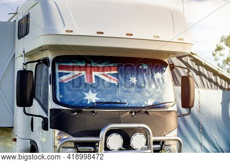 Motorhome Campervan With Flag Of Australia On The Windscreen At The Campground. Australian Camping A