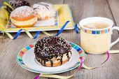 Chocolate and coconut donuts with carnival decoration. German traditional kreppel for carnival poster