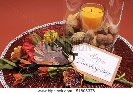 Beautiful Happy Thanksgiving Table Setting Centerpiece With Ornage Candle And Nuts In Decorative Gla