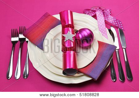 Modern Candy Fuschia Pink Christmas Table Setting With Cracker And Baubles, Plates And Cutlery, On A