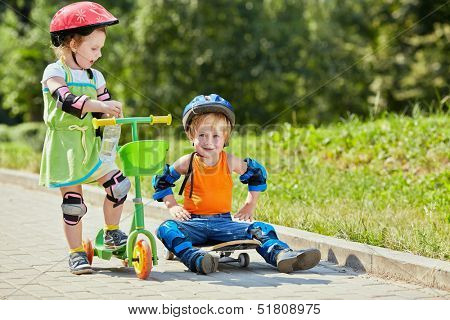 Little boy sits on skateboard with his arms akimbo ,little girl with three-wheeled scooter stands next to him