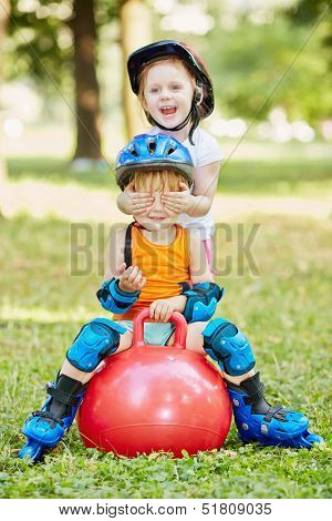 Little boy sits on red ball for jumping, girl closes his eyes with her hands, standing behind him
