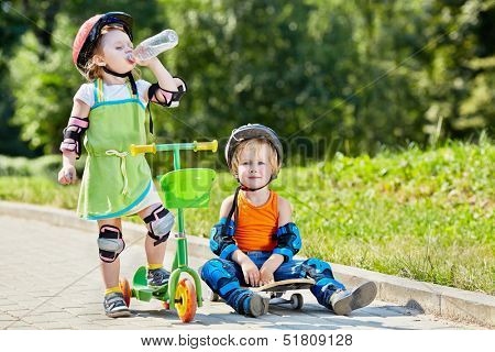 Little boy sits on skateboard next to little girl, who drinks water from plastic bottle, standing with three-wheeled scooter
