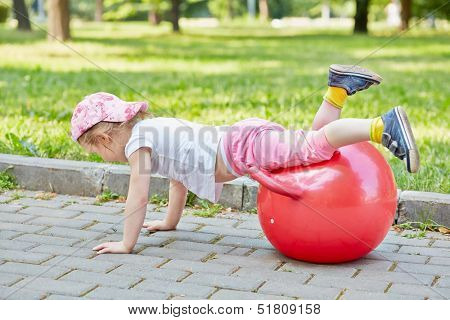 Little girl plays with red ball for jumping on  walkway in park, hands on ground, legs on ball
